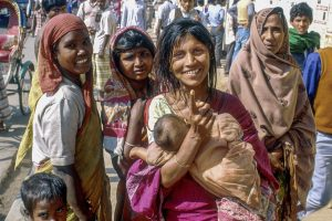 Bangladesh-Dhaka, Life in the slums. Woman with child greets the photographer.