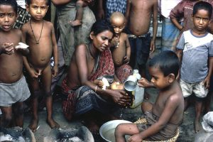 Bangladesh-Dhaka, Woman and children are treating a very sick baby in slum area