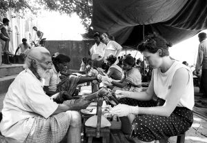 India-Kolkata, A volunteer treats a man with leprosy in the street.